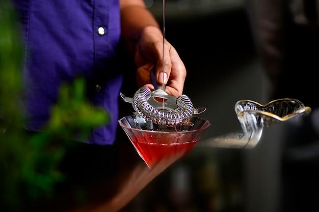 Бармен девушка переливает клубничный напиток в баре