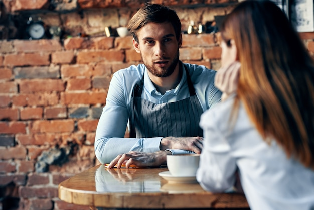 Bartender in gray apron sits at the table and client with a cup of coffee brick wall interior model