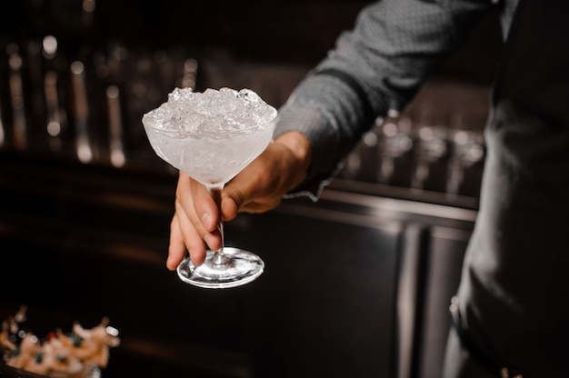 Bartender hand holding a cocktail glass with ice