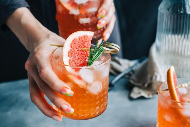 氷とローズマリーとグレープフルーツカクテルレモネードグラスを保持しているバーテンダーの手。