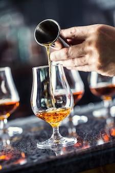 ナイトクラブ、バー、またはパブでアルコール飲料を注ぐバーテンダーの手。