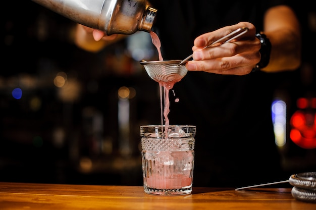 Bartender hand pouring pink cocktail drink in bar