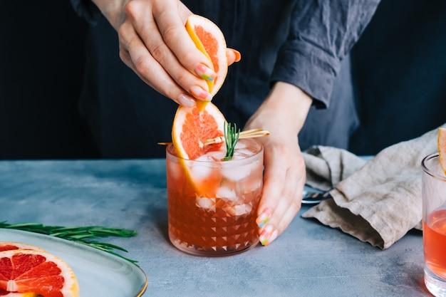 バーテンダーの手が新鮮なグレープフルーツのジュースを氷とローズマリーのカクテルレモネードで絞ります。