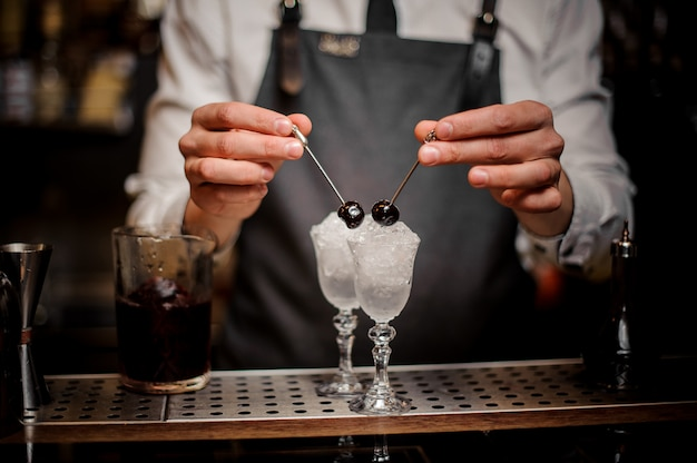 Bartender hands decorating two cocktail glasses with cherries