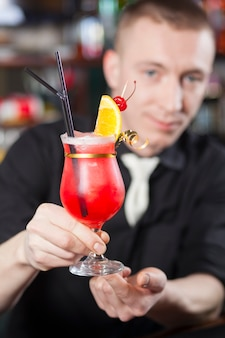The bartender hands a freshly prepared cocktail