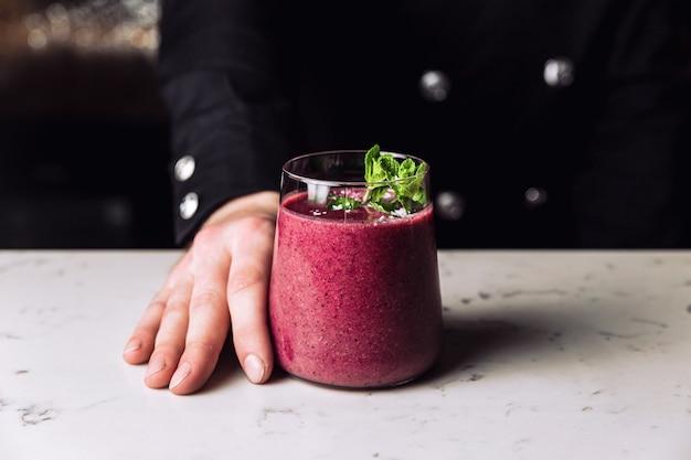 민트 장식, 대리석 테이블로 장식된 상쾌한 숲 과일 베리 스무디 칵테일 한 잔을 들고 있는 바텐더.