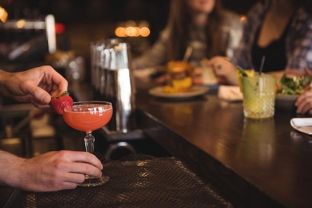 Barista che tiene cocktail al bancone del bar