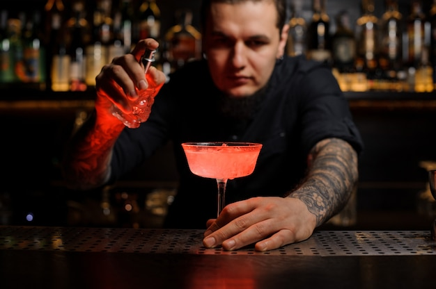 Bartender holding the delicious cocktail and the special vaporizer on the bar counter
