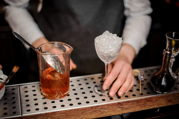 Bartender holding a glass filled with ice and alcoholic drink