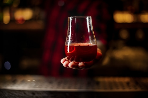 Bartender holding a glass of fresh and sweet tasty red cocktail with a slice of orange peel