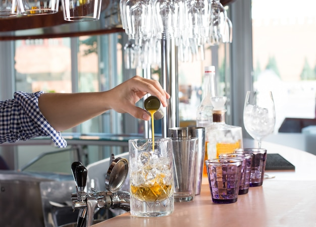 Bartender holding steel jigger and pouring orange liquor into the glass with ice.