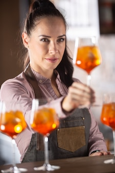 Bartender is checking the quality of an orange cocktail aperol spritz in the glass.
