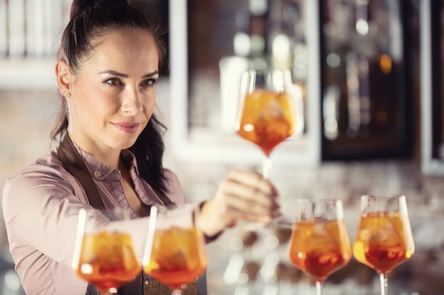 Bartender is checking the quality of an orange cocktail aperol spritz in the glass. Premium Photo