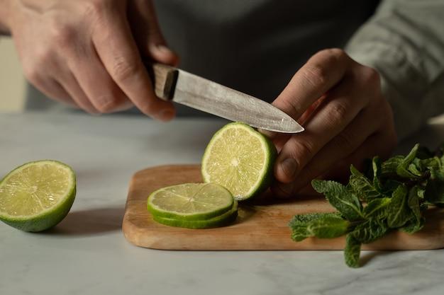 Бармен режет ножом сочный зеленый лайм на разделочной доске, а рядом лежит веточка мяты.
