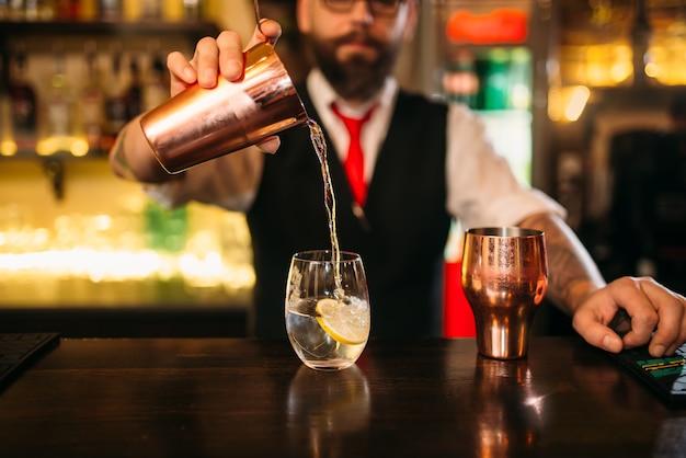 バーテンダーがカウンターでアルコールカクテルを作っています。