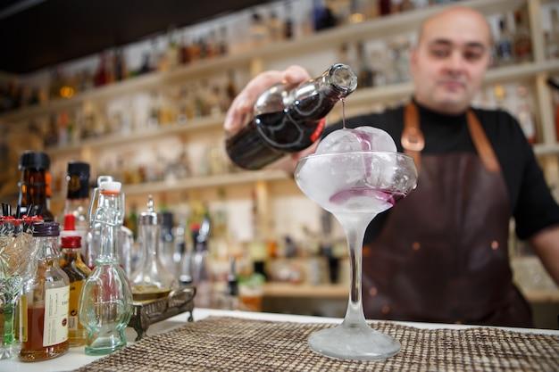バーテンダーは、巨大な氷、広角のイメージでグラスにワインを注いでいます。