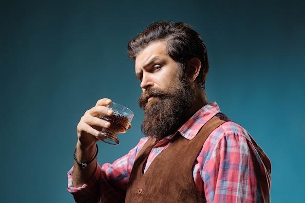 ガラスアルコール飲料でウイスキーカクテルを保持しているバーテンダーレザーエプロン