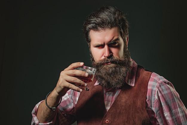 ガラスの古い伝統的なウイスキードリンク紳士でウイスキーカクテルを保持しているバーテンダーレザーエプロンは...