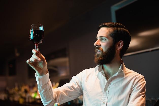 Barista guardando un bicchiere di vino rosso