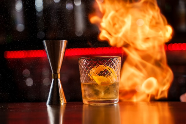 The bartender makes flame over a cocktail with orange peel close up.
