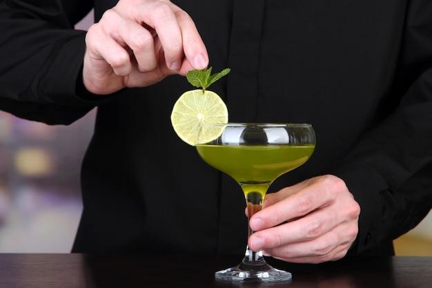 Бармен готовит и украшает коктейль