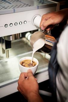 Бармен делает капучино в кафе