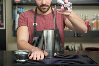 Bartender making cocktail at bar counter