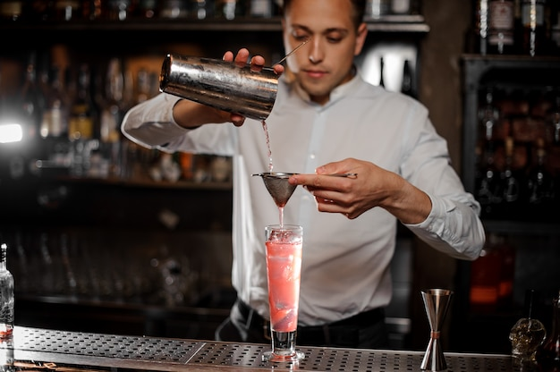Bartender making a fresh and cold strawberry mojito summer cocktail