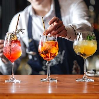 Бармен делает фруктовые алкогольные коктейли на деревянном столе