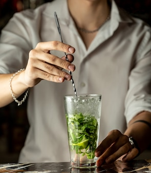 Bartender mixes mojito cocktail with metal spoon