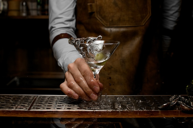 Bartender mixing a transparent alcoholic drink in the martini glass with one olive