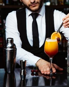 Бармен кладет ломтик апельсина на коктейль