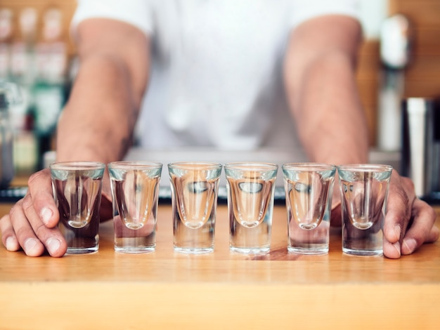 Bartender placing line of shot glasses on counter