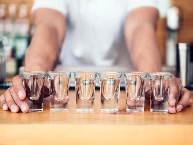 Bartender placing line of shot glasses on counter