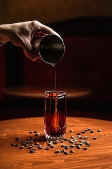 バーテンダーがシェーカーから氷の槍でコリンズのハイボールグラスにカクテルを注いでいます。木製のテーブルの周りのコーヒー豆。