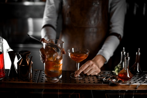 Bartender pouring alcohol cocktail with the strainer