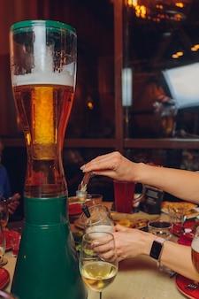 바텐더 유리 클로즈업에 맥주를 붓는. 길거리 음식.