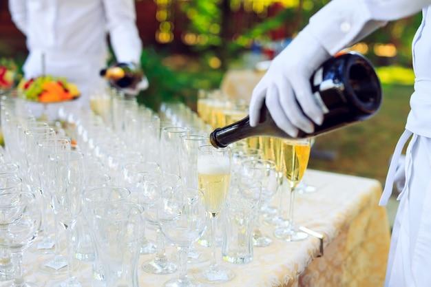 Бармен наливает шампанское в бокалы