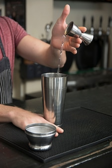 Bartender pouring cocktail in shaker at bar counter