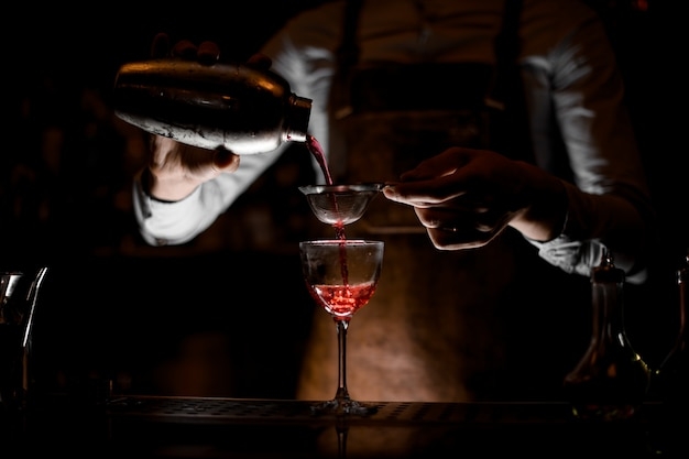 Bartender pouring cocktail with sieve in glass