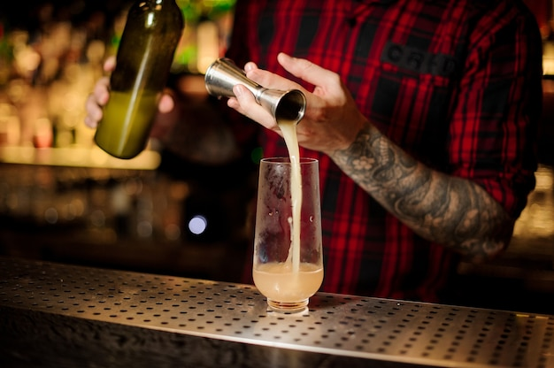 Bartender pouring a delicious trinidad swizzle cocktail from the steel jigger to a glass on the bar counter