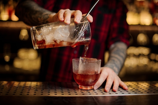 Bartender pouring a delicious vieux carre cocktail from the measuring cup to a glass on the bar counter