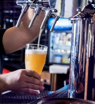 Бармен разливает разливное пиво по бокалам в баре. ресторан.