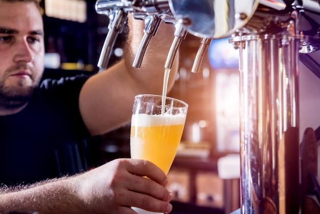 Bartender pouring draft beer at glasses in the bar. restaurant.