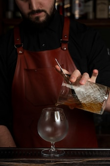 Bartender pouring drink from crystal glass into snifter