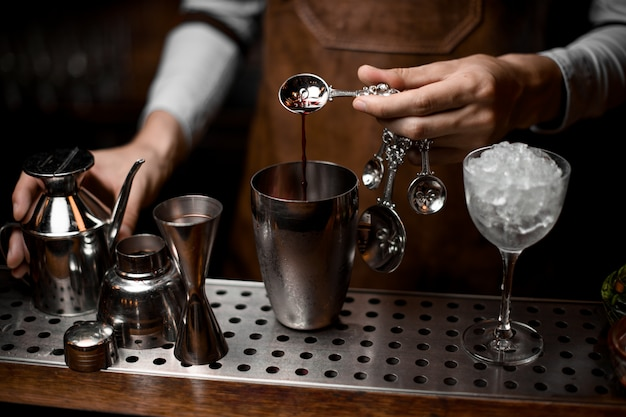 Bartender pouring an essence from the spoon to the steel shaker