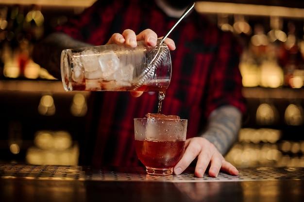 バーテンダーが新鮮で強いウイスキーカクテルを大きな角氷の入ったグラスに注ぐ