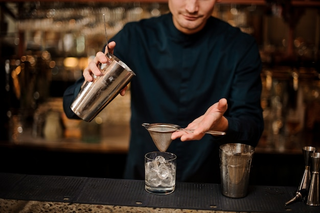 Bartender pouring fresh drink from a shaker into a glass using strainer