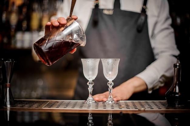 グラスに新鮮な夏のアルノーカクテルを注ぐバーテンダー