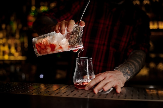 Bartender pouring fresh and tasty bittersweet red cocktail into an empty cocktail glass on bar